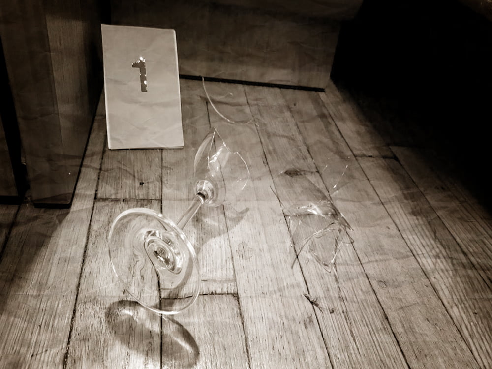 Na podłodze leży rozbity kieliszek dowina orazpolicyjna tabliczka dooznaczania dowodów znumerem jeden.